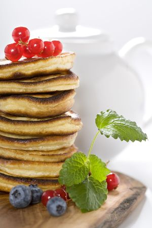 freshly prepared: Stack of freshly prepared pancakes with berries and witn tea pot on a background