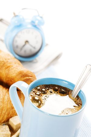 coffee, alarm clock, newspaper, telephone and fresh croissants in a kitchen photo