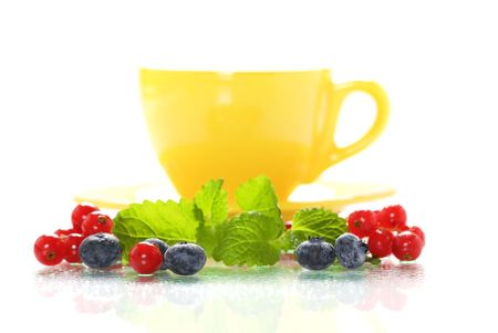 fresh berries, mint and yellow tea cup photo