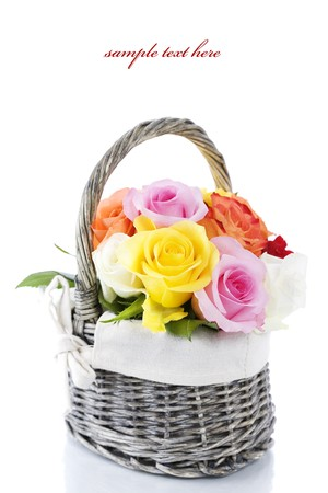 Multicolored roses in a basket over white  (with sample text)  photo