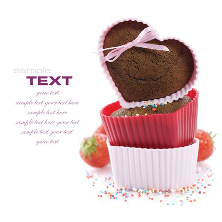 chocolate sprinkles: A pile of three chocolate heart shape muffins in  silicone molds with strawberry and sprinkles Stock Photo