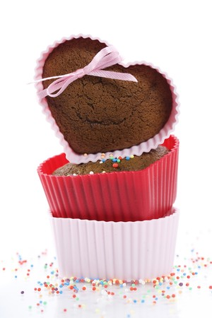 silicone: A pile of three chocolate heart shape muffins in  silicone molds with strawberry and sprinkles Stock Photo