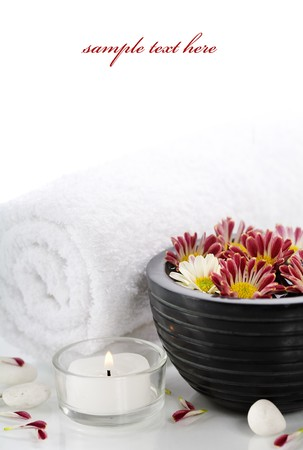 bowl of water, towel, candle and flowers over white with copyspace (with sample text)