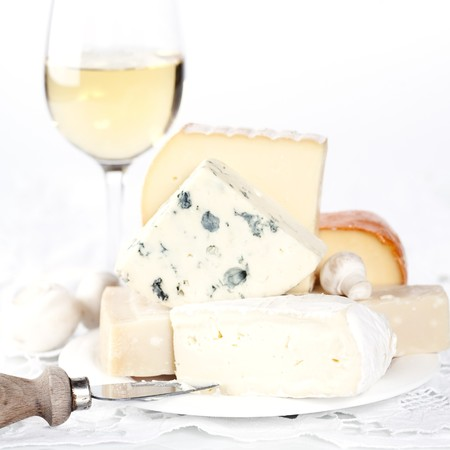 White wine and Various types of cheese on a plate photo