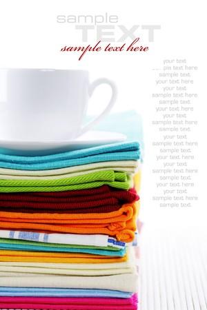 Haufen von Leinen Küchentücher und Tasse Tee oder Kaffee over White (mit Beispiel-Text)