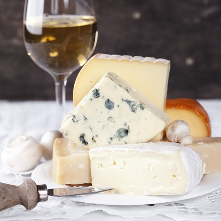 dutch: White wine and Various types of cheese on a plate Stock Photo