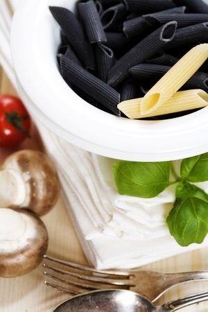 Penne, tomato, mushrooms and basil on the table photo
