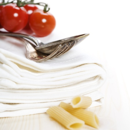 Spoon, fork, napkins and pasta ingredients over white photo