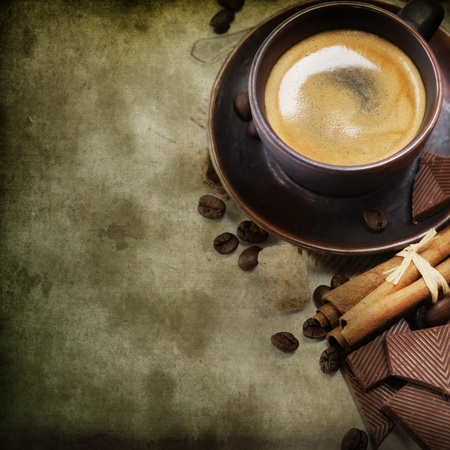 Closeup shot of freshly prepared cup of italian espresso with cinnamon, coffe beans, brown sugar and chocolate over white (with sample text) photo