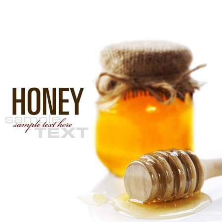 pot of gold: Full honey pot and honey stick over white (with sample text)