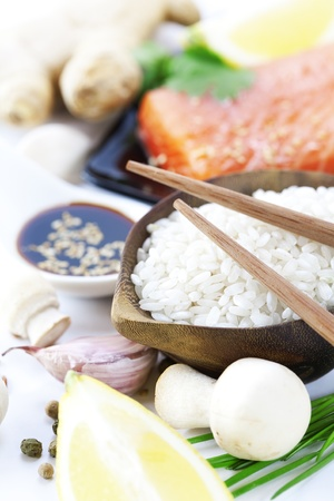 sause: traditional asian ingredients (Fresh salmon steak filet, uncooked rice, ginger, garlic, mushrooms, soy sause and chopsticks) over white