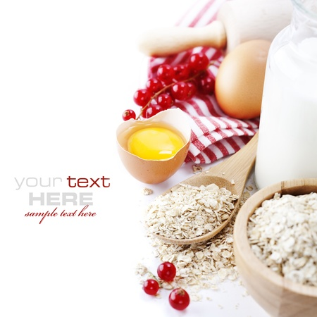 Fresh ingredients for oatmeal cookies (oat flakes, eggs, milk, fresh ripe currant) over white with sample text photo