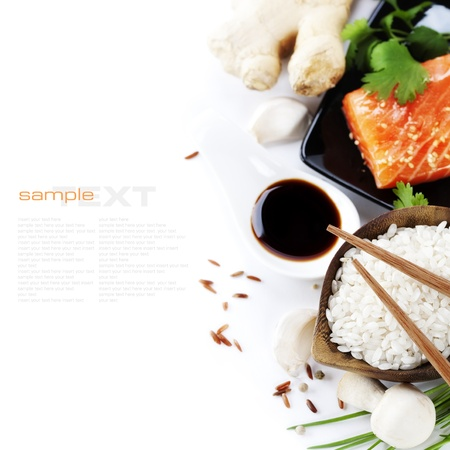 traditional asian ingredients (Fresh salmon steak filet, uncooked rice, ginger, garlic, mushrooms, soy sause and chopsticks) over white with sample text photo