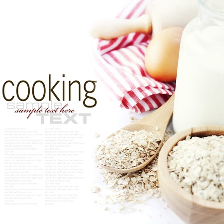 milk and cookies: Fresh ingredients for oatmeal cookies (oat flakes, eggs, milk) over white with sample text