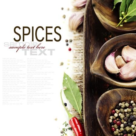comida gourment: cuencos de madera con hierbas frescas y especias (pimienta, ajo, hojas de laurel) con texto de ejemplo Foto de archivo