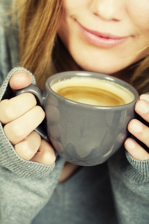 woman holding cup of coffee and smiles Stock Photo