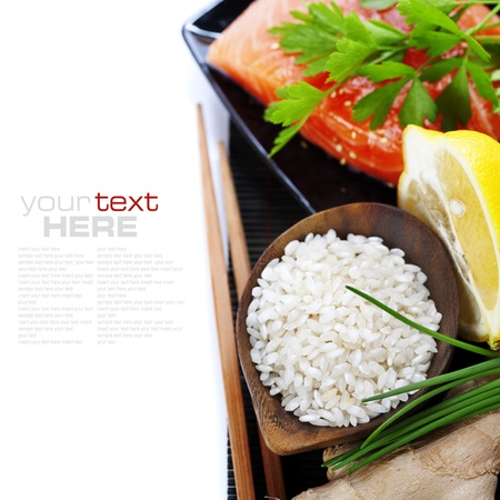 sushi roll: traditional asian ingredients (Fresh salmon steak filet, uncooked rice, ginger, lemon,   and chopsticks) over white with sample text