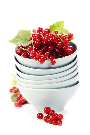 red currant: Stack of bowls and ripe red currant berries over white Stock Photo