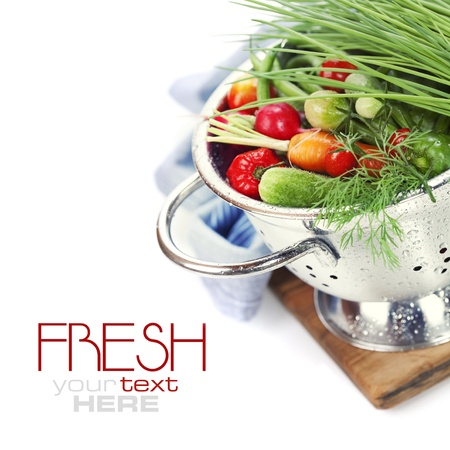 a colander: Fresh vegetables in metal colander over white (with sample text) Stock Photo
