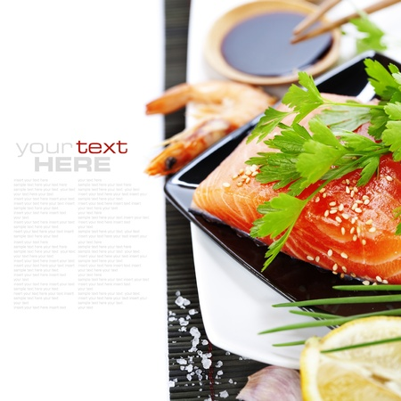 comida japonesa: traditional asian ingredients (Fresh salmon steak filet,  ginger, lemon,  soy sause and chopsticks) over white with sample text Imagens