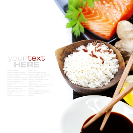 sause: traditional asian ingredients (Fresh salmon steak filet, uncooked rice, ginger, lemon,  soy sause and chopsticks) over white with sample text
