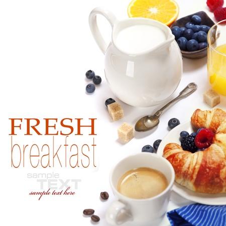 Délicieux petit déjeuner avec des produits frais du café, du lait, des croissants frais et de fruits (avec échantillon de texte)