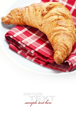 fresh croissant on plate over white with copyspace photo
