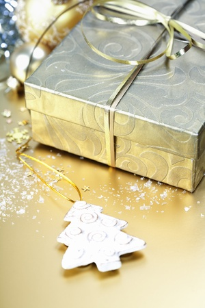 Golden gift box with golden ribbon and christmas decorations photo