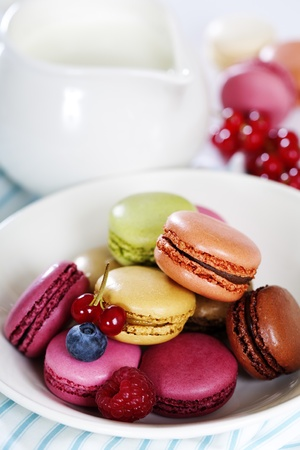 Colorful macaroons in a white plate and fresh milk photo
