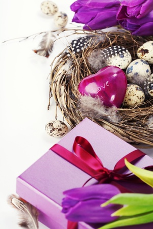 easter eggs with purple tulip flowers  and gifts on white background photo