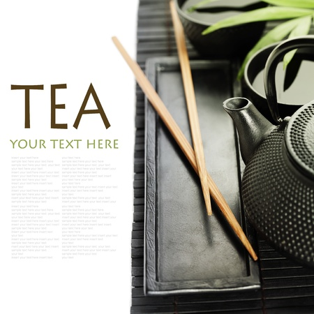 wooden insert: Asian tea set on bamboo mat (Green tea, palm leaf and chopsticks) with sample text Stock Photo