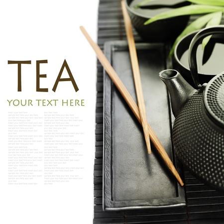 Thé asiatique mis sur le tapis en bambou (thé vert, feuille de palmier et des baguettes) avec échantillon de texte