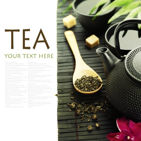 Asian tea set on bamboo mat (Green tea, orchid and chopsticks) with sample text photo