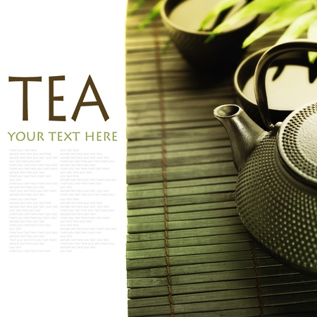 Asian tea set on bamboo mat(Green tea, palm leaf and chopsticks) with sample text photo