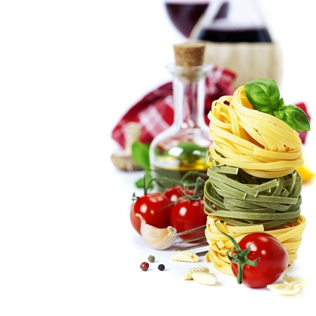Pasta italiana (con tomate, aceite de oliva y albahaca) y el vino sobre un fondo blanco Foto de archivo