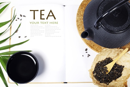 Open notebook and Asian tea set on  white background  (with easy removable sample text)    photo