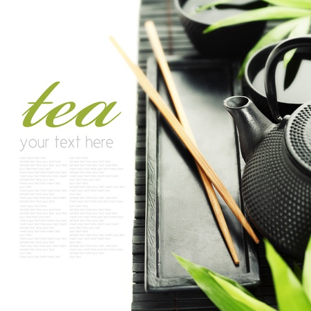 Asian tea set on bamboo mat (Green tea, bamboo leaf and chopsticks) with sample text photo