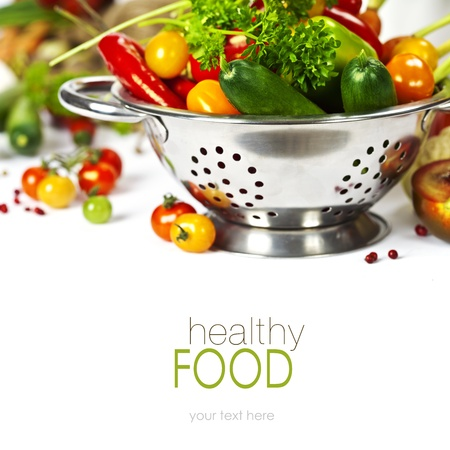 a colander: Fresh vegetables in metal colander over white (with easy removable text) Stock Photo