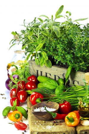wooden insert: herbs in the box and fresh vegetables over white Stock Photo