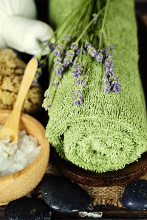 Fresh  and dried lavender flowers, towel, salt, zen stones  and  Herbal massage balls over wooden surface photo