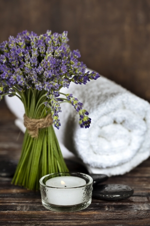 Fresh  lavender flowers, zen stones, essential oil, candle and towel over wooden surface photo