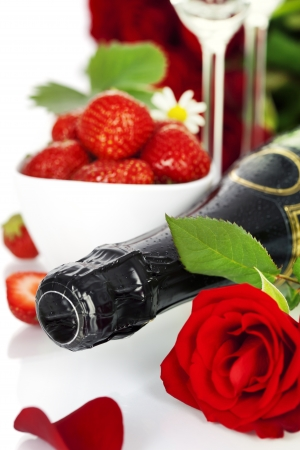 Romantic still life with champagne, strawberry and beautiful red roses over white photo