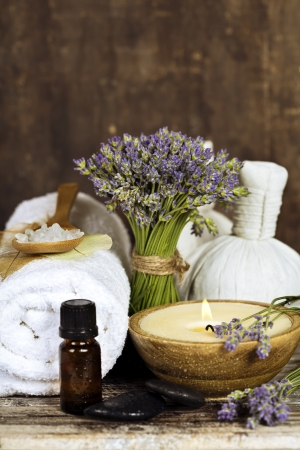 Fresh  lavender flowers, zen stones, essential oil, candle, Herbal massage balls  and towel over wooden surface photo