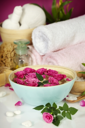 Spa setting with flowers, sea salt, towels and essential oil photo