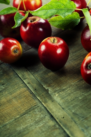 red apples with leaves on wooden table. With copyspace  photo