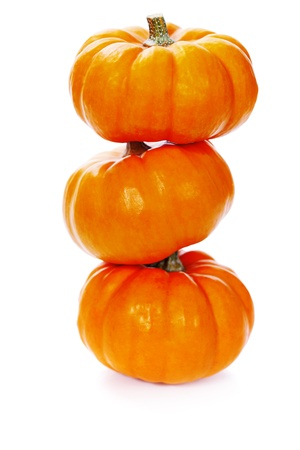 Three stacked mini pumpkins over white  photo