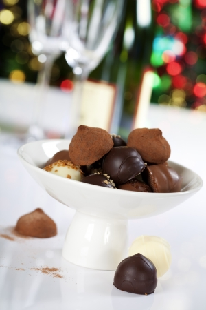 champagne truffles chocolate: Delicious chocolate pralines and truffles on Christmass tree background