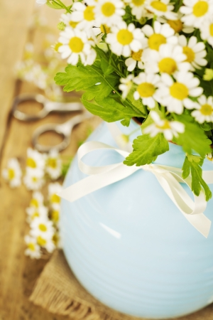 Beautiful flowers in a vase on an old table photo