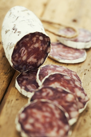 Close-up traditional sliced meat sausage salami on wooden board  photo
