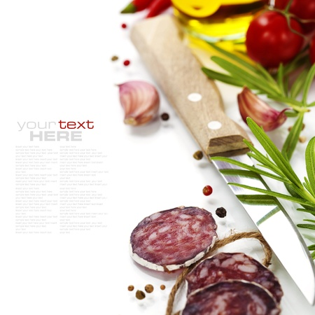 air dried salami: Close-up traditional sliced meat sausage salami with knife and vegetables Stock Photo